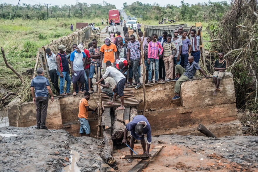 After the cyclone knocked out a bridge in Macomia, people worked to build a makeshift replacement out of logs and planks.