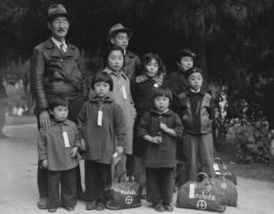Hayward, California. Members of the Mochida family awaiting evacuation bus. Identification tags are used to aid in keeping the family unit intact during all phases of evacuation. Mochida operated a nursery and five greenhouses on a two-acre site in Eden Township. He raised snapdragons and sweet peas. Evacuees of Japanese ancestry will be housed in War Relocation Authority centers for the duration.