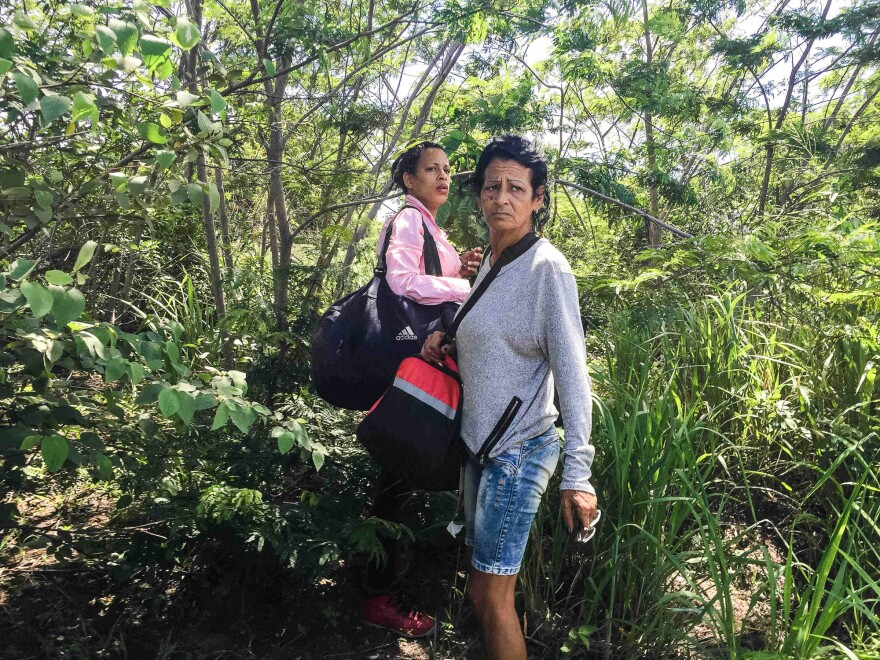 On the very first day of the journey, Marta and Liset stand nervously, waiting for a signal to run to awaiting cars and cross illegally from Guyana to Brazil.