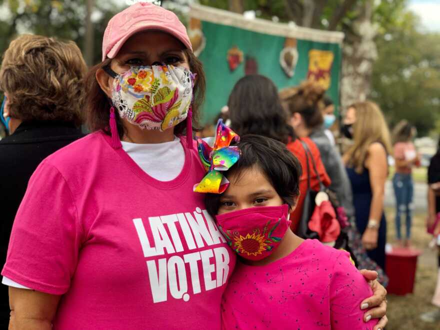 Oak Cliff resident Marie Lou Paras wears a 'Latinas Vote' shirt and stands next to her 7 year old granddaughter Makayla in front of an event encouraging voter turnout.