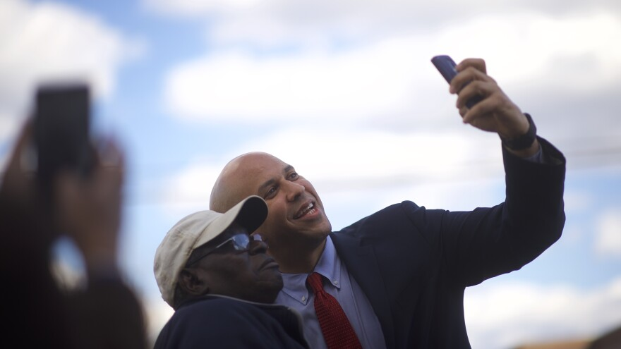Sen. Cory Booker takes a photo with a supporter as he arrives at a campaign event for former Secretary of State Hillary Clinton in February.