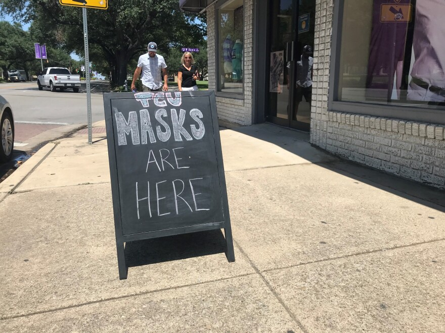 """In this photo, a chalkboard sign with the words """"TCU masks are here"""" stands on the sidewalk outside a store."""