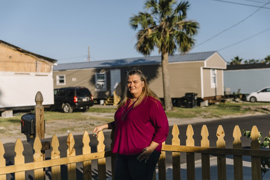 Christina Harding stands in front of the Habitat for Humanity home where she's lived since 2016 in Panama City, Fla. Last year Harding rode Hurricane Michael with her family in the house. Much of her neighborhood still shows signs of massive damage.