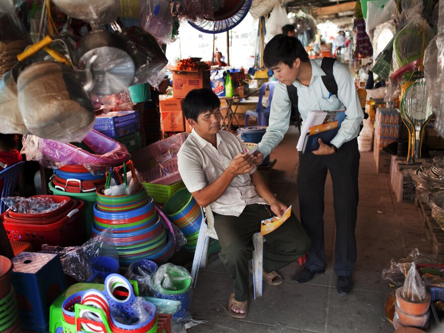 Deuk Chamnan (right), a credit officer at First Finance, speaks with a potential client while passing out leaflets at Century Market in Phnom Penh. First Finance also advertises on the radio.