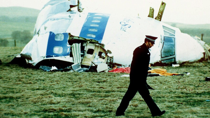 A police officer walks on Dec. 21, 1988, by the nose of Pan Am Flight 103 near Lockerbie, Scotland, where it lay after a bomb aboard exploded, killing a total of 270 people.