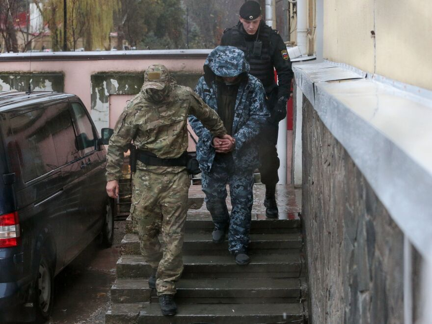 A detained Ukrainian sailor is escorted to a car after a court hearing in Simferopol, Crimea, on Wednesday. On Sunday, Russian forces fired on, boarded and captured three of Ukraine's boats.