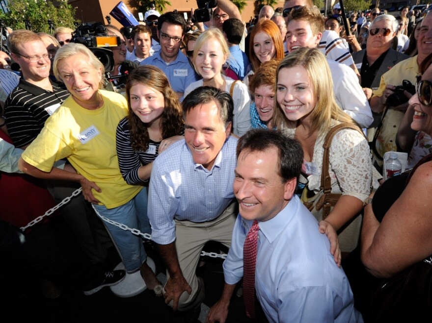 <p>Mitt Romney and Nevada Lt. Gov. Brian Krolicki (r) take photos with supporters as Romney opens his state headquarters in Las Vegas, October 17, 2011.</p>