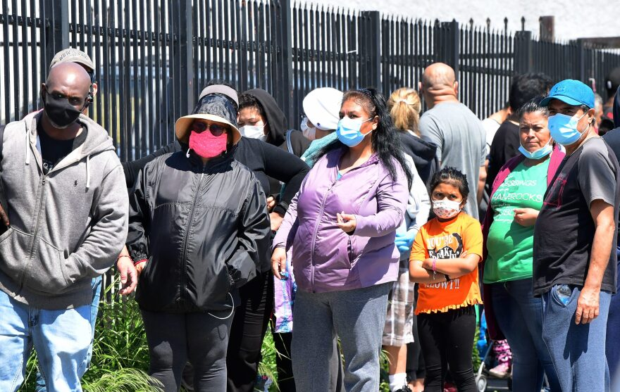 People wear their face masks as they wait in an emergency food distribution line outside the 88th Street Temple Church of God in Christ on April 14, 2020, in Los Angeles, California, during the coronavirus pandemic. (FREDERIC J. BROWN/AFP via Getty Images)