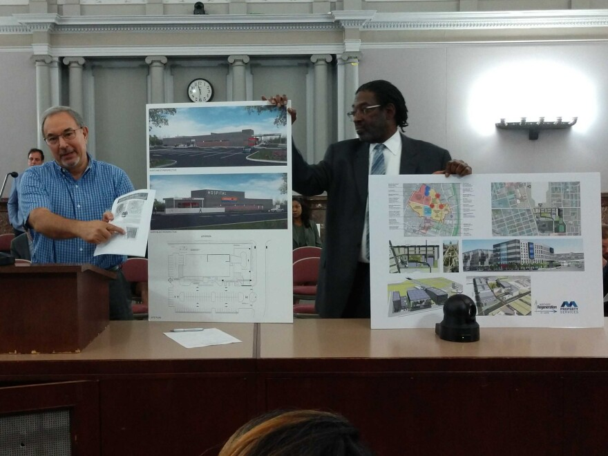 Bill Laskowsky (left) and Darryl Piggee, representatives of the Northside Regeneration urgent care project, show renderings for the proposal.