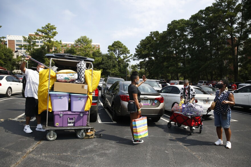 The Lawrence family moves their youngest daughter, Kelsey (center), into her new dorm room. The university allowed each student only two move-in helpers, leaving mom Vanessa Lawrence (far right) to wait outside.