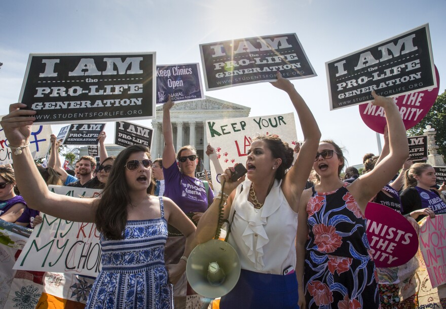 Reagan Barklage of St. Louis, center, and other anti-abortion activists demonstrate in front of the Supreme Court in Washington, Monday, June 27, 2016, as the justices struck down the strict Texas anti-abortion restriction law known as HB2. The justices voted 5-3 in favor of Texas clinics that had argued the regulations were a thinly veiled attempt to make it harder for women to get an abortion in the nation's second-most populous state.