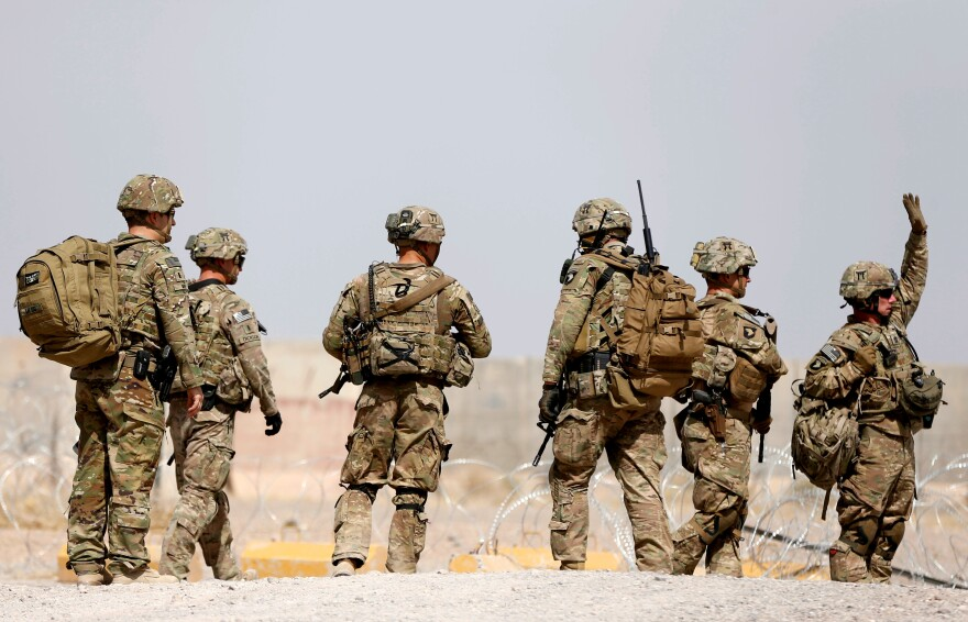 U.S. troops walk outside their base in Uruzgan province, Afghanistan, on July 7. President Trump has presented a new approach to the conflict there.