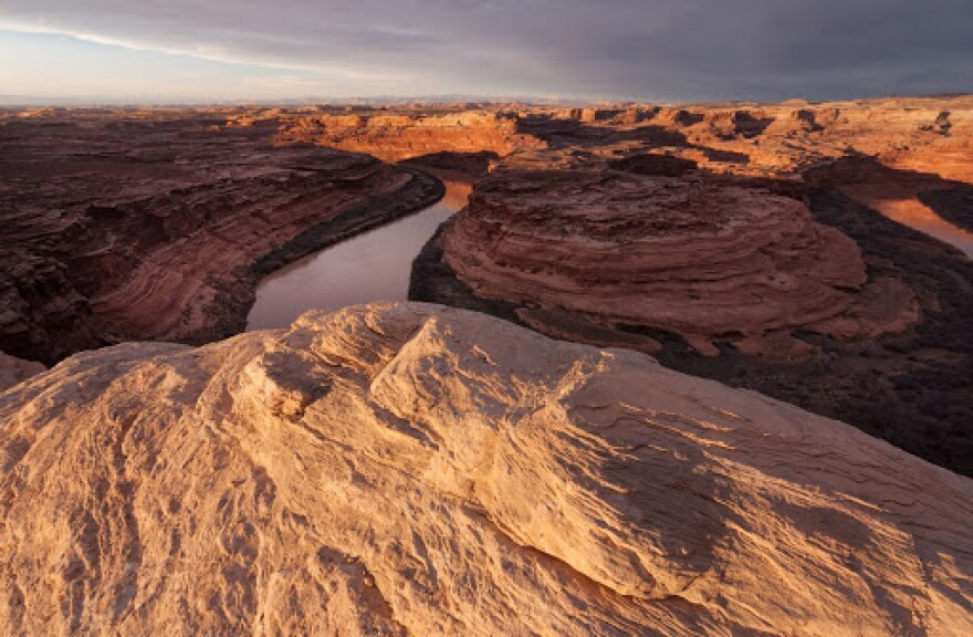 A winding river cuts through red rock canyons