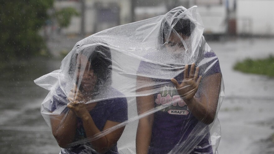 Residents use plastic sheets to protect them from rains and strong winds brought by Typhoon Hagupit in Legazpi, Albay province, eastern Philippines on Sunday.