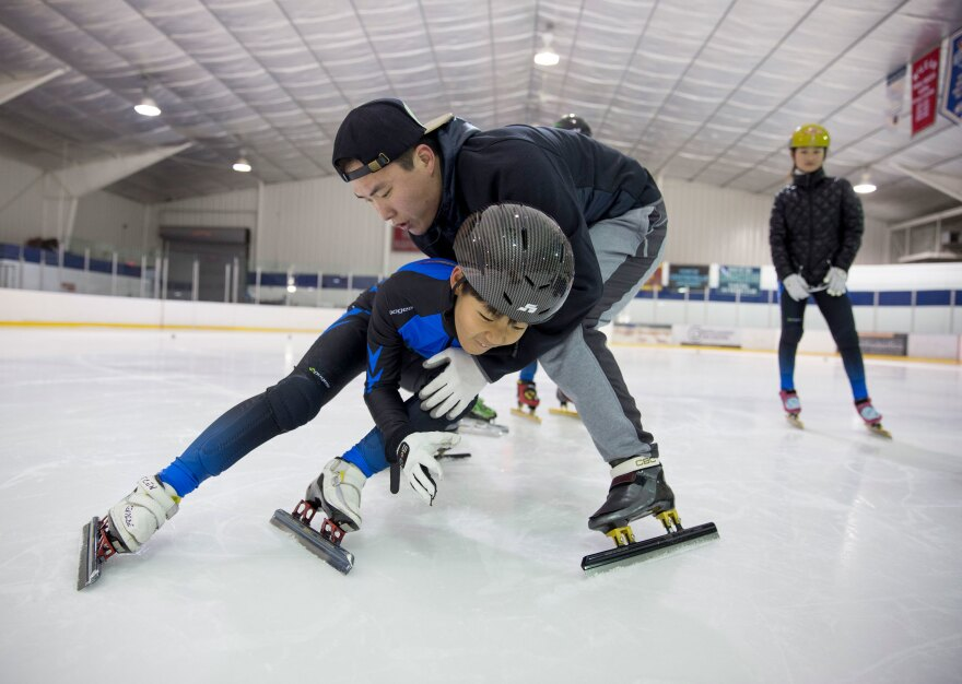 Soo An Yoo, a coach with Dominion Speedskating from South Korea, helps David Chun, 9, learn how to do tight turns as Kyubin Oh looks on.