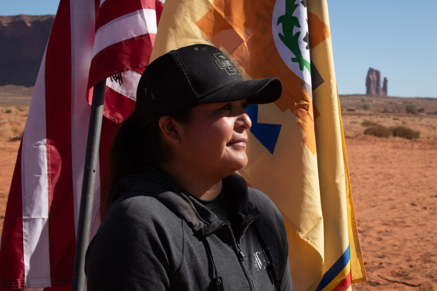 Photo of a woman in a baseball hat stands in front of two flags in Monument valley, with a sandstone formation in the background.