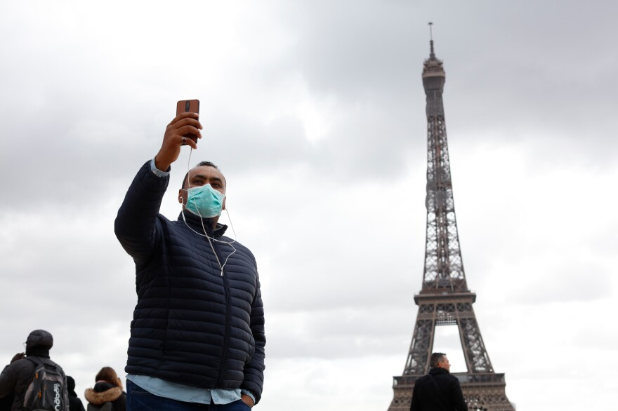 People with protective masks walk in front of the Eiffel Tower in Paris on March 9. The new coronavirus has had an impact on international travel.