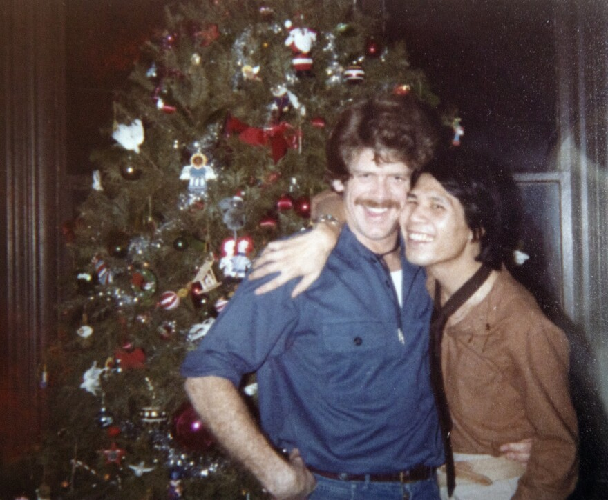 Yorkie Louie with his partner Michael Faino in front of a Christmas tree.