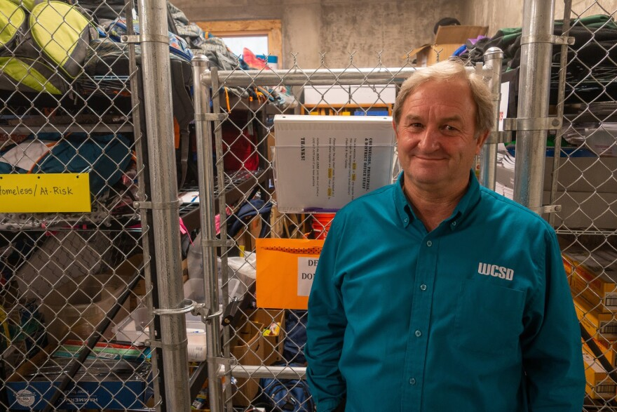 Photo of a county employee standing in front of a chain-linked fence storage, which is filled with donated backpacks and school supplies.
