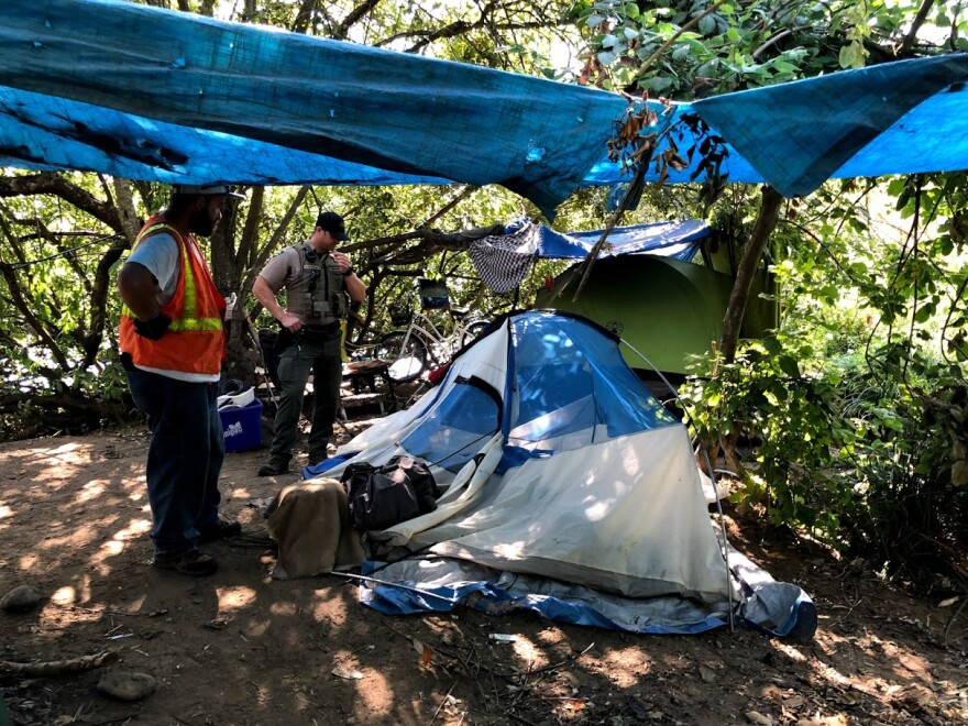 A homeless camp outside Jacob Maurie Park is visited by clean-up crews.