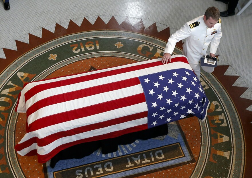 Jack McCain, son of Sen. John McCain, R-Ariz., touches his father's casket during a memorial service at the Arizona Capitol on Wednesday in Phoenix.