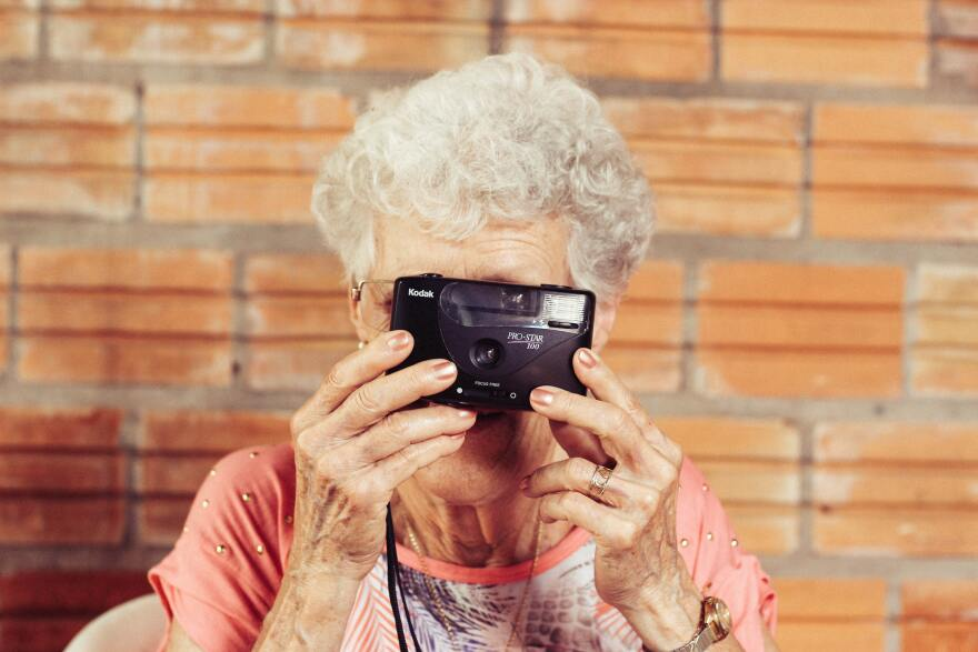 Old woman holds up a film camera to her face