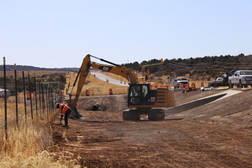 A yellow crane shovels dirt near the opening of a tunnel under the highway.