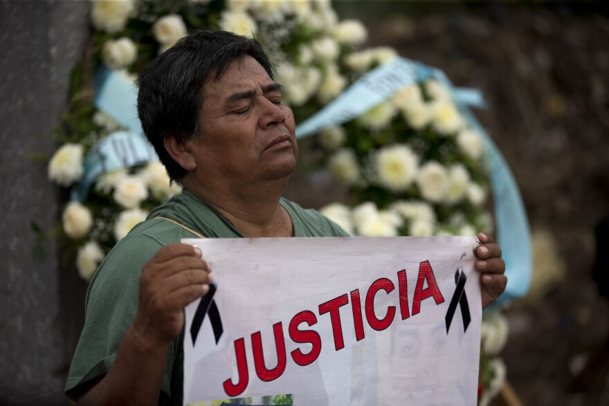 "A man holds a banner that reads in Spanish ""Justice,"" during a march by parents and relatives of 43 missing students who were killed, in Iguala, Mexico."