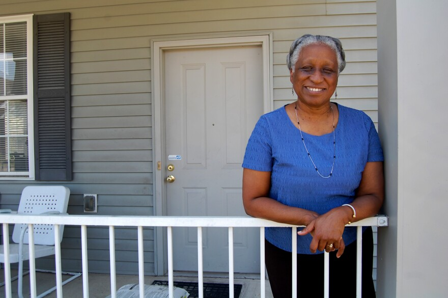Annie Haigler poses on her front porch in the Park DuValle neighborhood of Louisville. Haigler says she wishes her neighborhood had more trees.