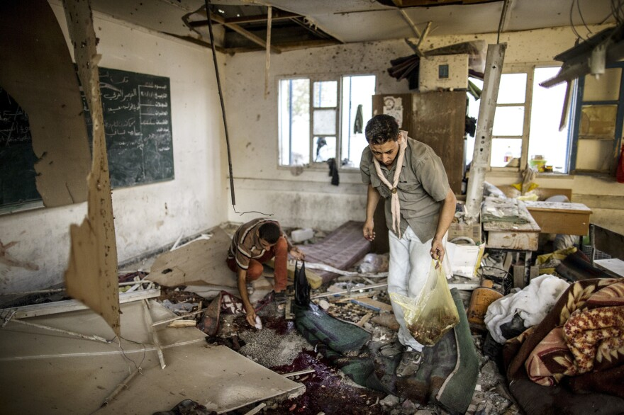 Palestinians collect human remains from a classroom inside Jabaliya school after it was hit by shelling on July 30, 2014.