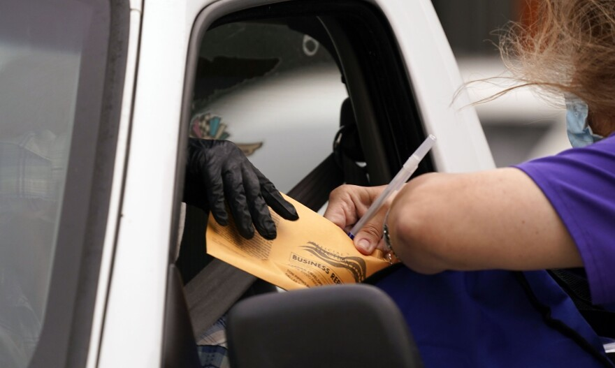 Hand reaching out car window to give orange ballot to masked election worker.