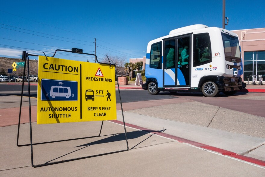 A yellow caution sign warns of an autonomous shuttle, which is in the background.