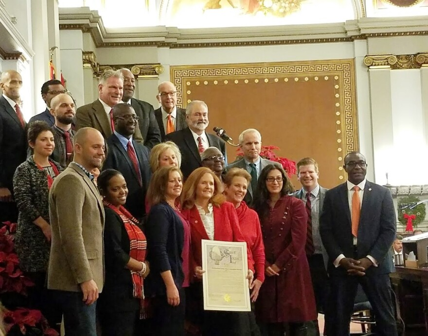 Alderman Donna Baringer D-16th Ward (center) receives a resolution from her colleagues on Dec. 16, 2016, her last day at the Board of Aldermen.