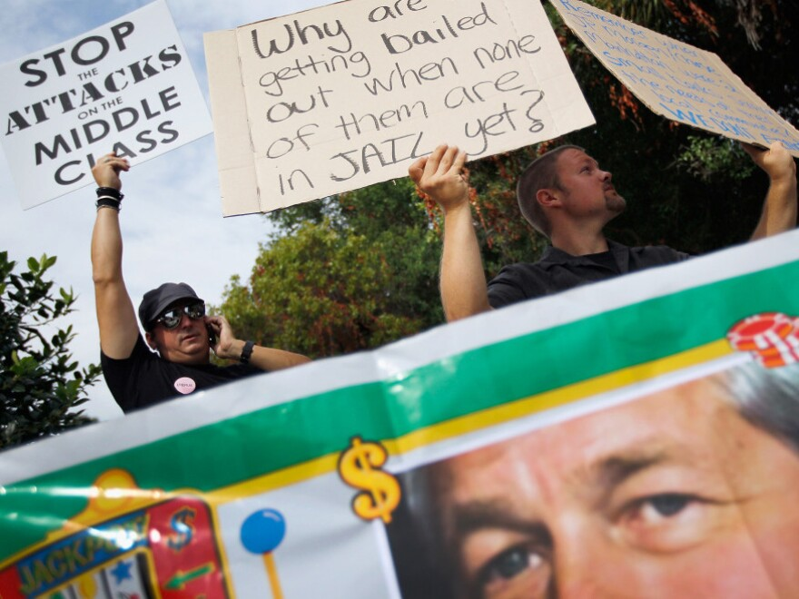 Standing behind a banner with a picture of J.P. Morgan Chairman and CEO James Dimon, protesters gathered outside the bank's annual meeting today in Tampa.