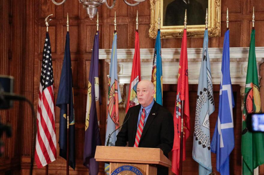 Montana Gov. Greg Gianforte stands in the state Capitol building flanked by tribal, state and the American flags.