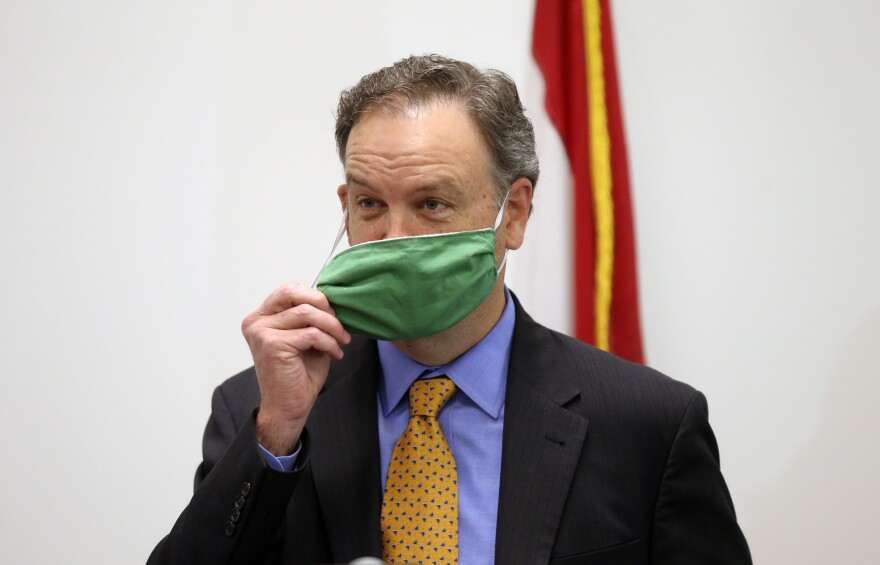 St. Louis County Executive Sam Page removes his mask before talking with reporters on May, 8, 2020.