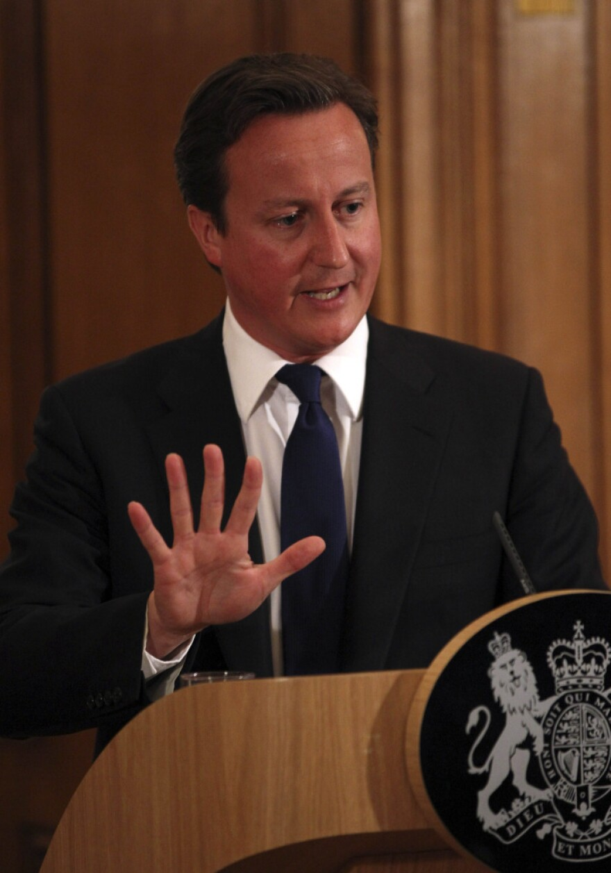 Britain's Prime Minister David Cameron promises a full investigation into the phone hacking and police bribery scandal that led to the collapse of the <em>News of the World</em> tabloid, at a press conference in London on Friday.