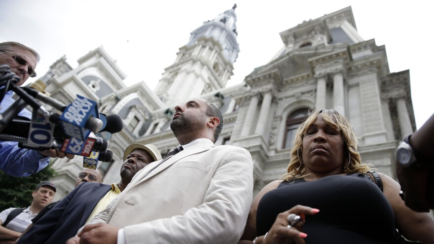 Tanya Brown-Dickerson (right), the mother of Brandon Tate-Brown, who was shot by Philadelphia police last December, listens to attorney Brian Mildenberg during a news conference on June 15 outside Philadelphia's City Hall. Brown-Dickerson is suing the city over the fatal shooting of her son. The police department did not initially name the officer who shot him, sparking protests.