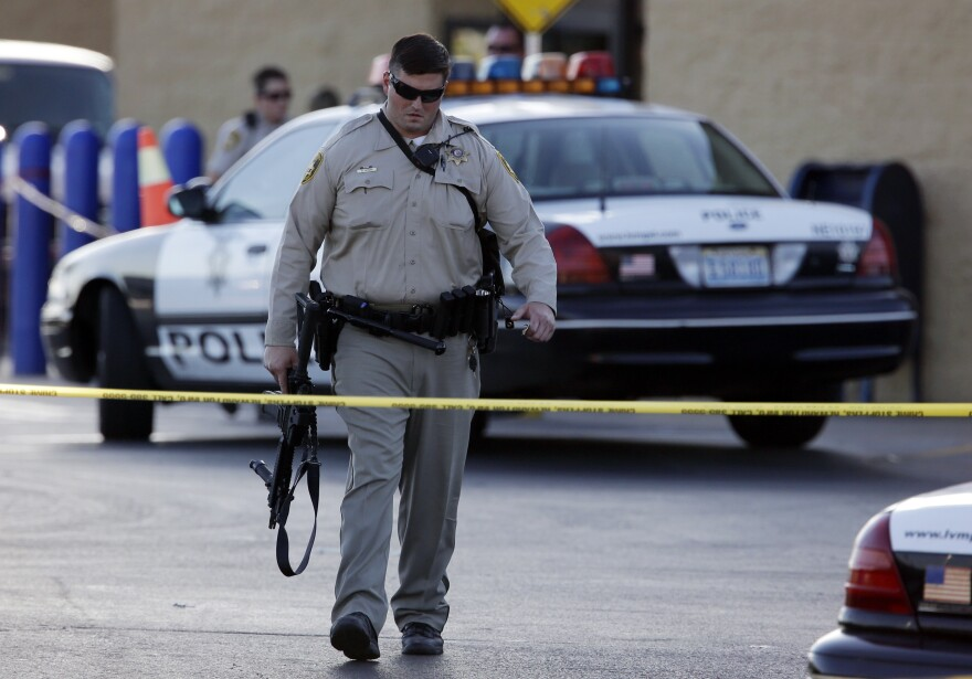 A Las Vegas police officer walks away from the scene of a shooting near a Wal-Mart on Sunday.
