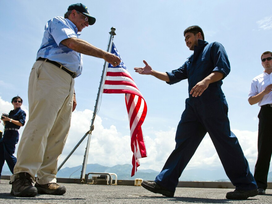 U.S. Defense Secretary Leon Panetta hands out coins to members of the crew as he visits USNS Richard E. Byrd in Cam Ranh Bay, Vietnam, on Sunday. Panetta toured the former U.S. air and naval base in the bay, becoming the most senior American official to go there since the war ended.