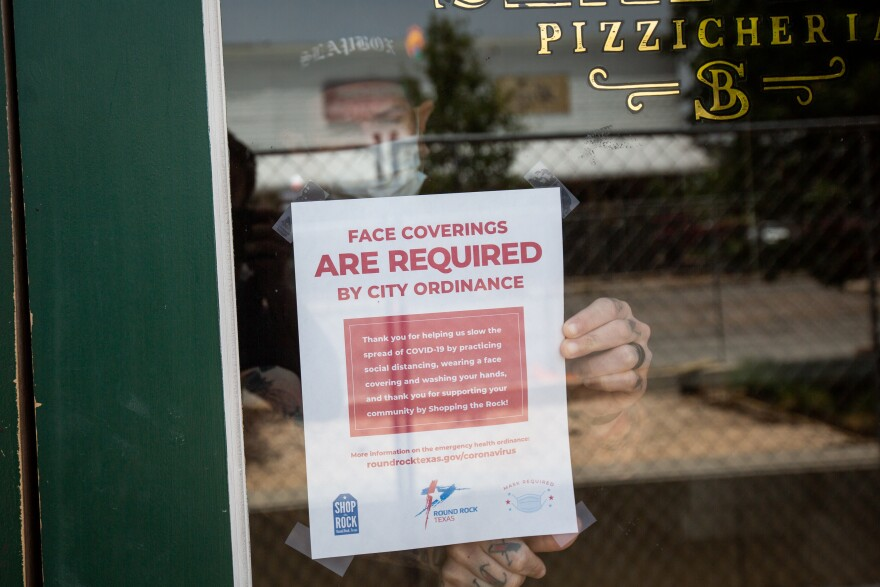 An employee at Slapbox Pizzicheria in Round Rock posts a sign saying face coverings are required.