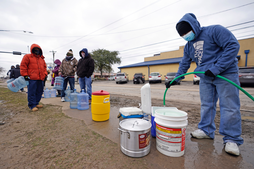 A man fills a cooler with water from using a hose from a public park spigot Thursday, Feb. 18, 2021, in Houston. (David J. Phillip/AP)