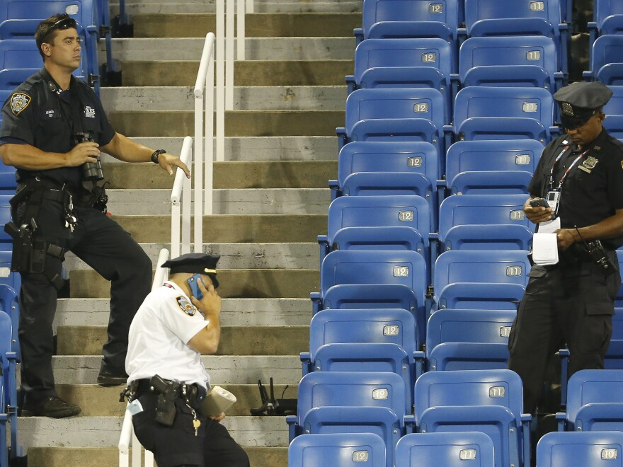 Police officers stand beside the remains of a drone that crashed into an empty section of seats at the U.S. Open on Thursday.