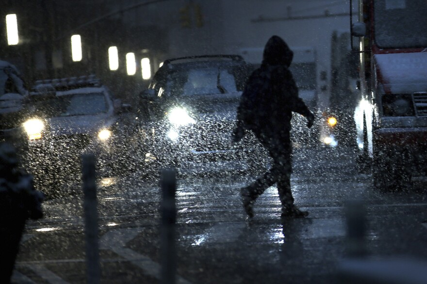 A man is silhouetted by car headlights as he crosses the streets of lower Manhattan during a snow storm on Thursday, Nov. 15, 2018, in New York. (Wong Maye-E/AP)