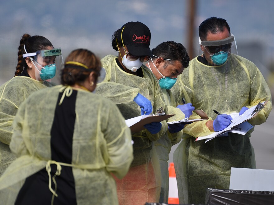 Medical personnel from Riverside University Health Systems hospitals administer a coronavirus test to an individual during drive-through testing in the parking lot of Diamond Stadium on March 22 in Lake Elsinore, Calif.