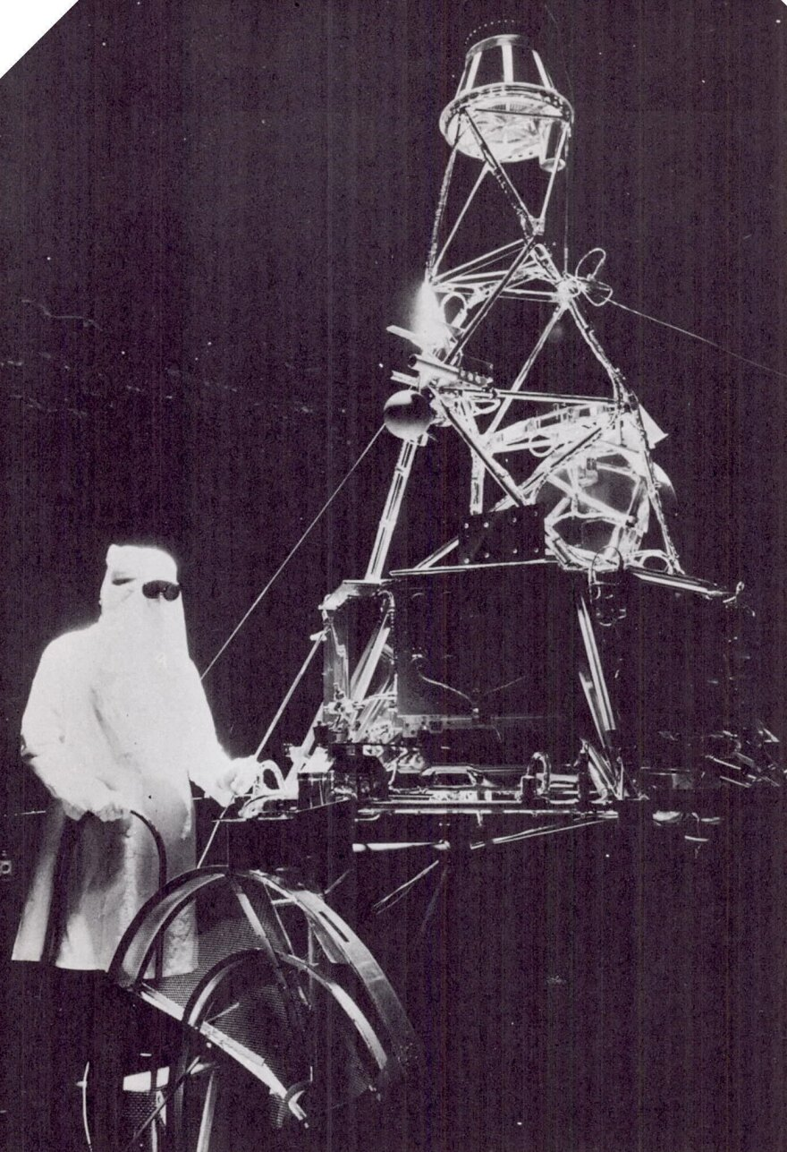 A technician wears a hood and protective goggles while working with a full-scale model of the Mariner spacecraft in a space simulator chamber at the Jet Propulsion Laboratory in Pasadena, Calif., in 1962.