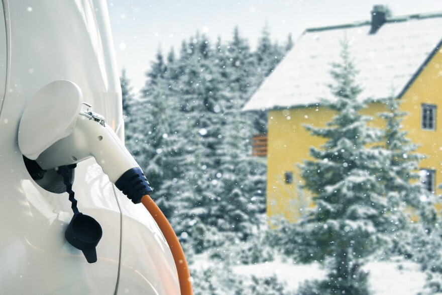 A close up of an electric car charging with snowy landscape in the background.