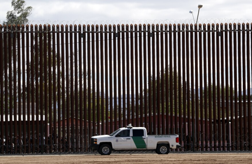 A U.S. Customs and Border Protection vehicle sits near the wall as President Trump visits a new section of the border wall with Mexico in El Centro, Calif., on April 5. This area is one where the Pentagon will spend more resources shifted away from military construction projects.