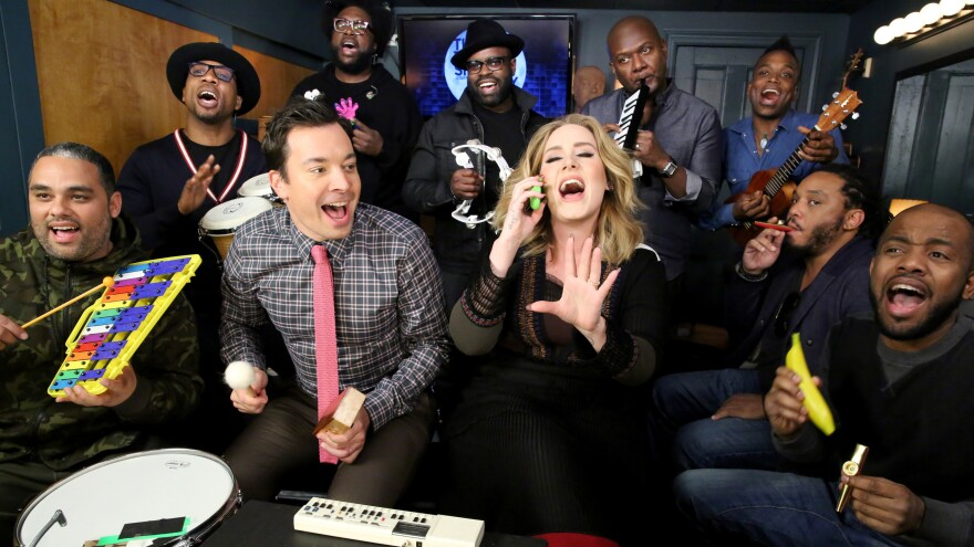 <em>The Tonight Show</em>'s Jimmy Fallon and house band The Roots sing with Adele during the show's Music Room segment.