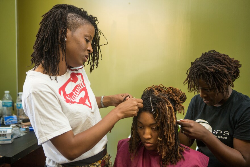 Tameka Stigers, left, and Ivy Perry, right, braid LaQuinn Laws hair in June 2015 in St. Louis.